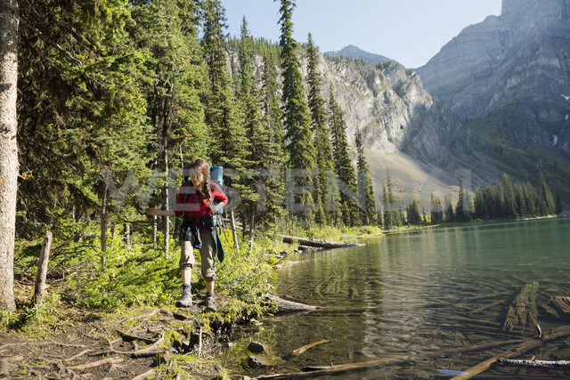 Woman hiking at sunny remote lakeside - HEROF14209 - Hero Images/Westend61
