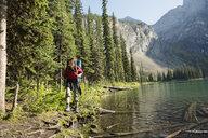 Woman hiking at sunny remote lakeside - HEROF14209