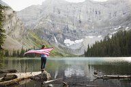 Woman holding American flag on rock at remote mountain lake - HEROF14212