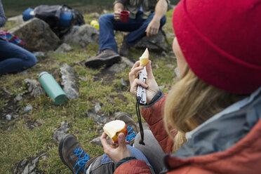 Woman eating apple at campsite - HEROF14218