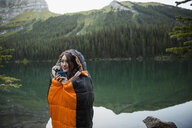 Woman standing in sleeping bag at remote lakeside - HEROF14227