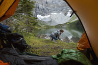Woman at remote lakeside outside of camping tent - HEROF14230
