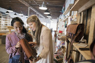Women friends shopping browsing leather handbag in shop - HEROF14233