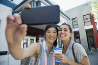 Women friends taking selfie with camera phone holding tickets outside movie theater - HEROF14242