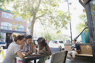 Women friends drinking coffee and using digital tablet at urban sidewalk cafe - HEROF14245