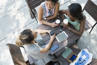 Women friends drinking coffee and using digital tablet at urban sidewalk cafe - HEROF14248