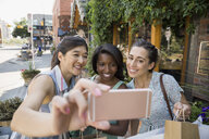 Women friends taking selfie with camera phone on sidewalk - HEROF14251