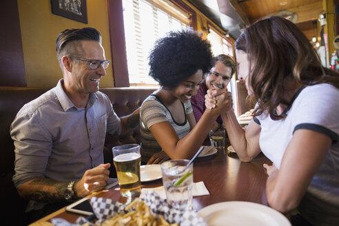 Women arm wrestling at table in bar - HEROF14257