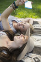 Women friends laying on blanket taking selfie with camera phone - HEROF14263