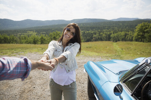 Wife leading husband by the hand near convertible at rural overlook - HEROF14266