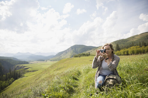 Woman hiking using camera in remote sunny rural field - HEROF14269