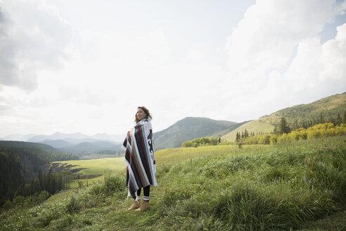 Woman wrapped in blanket in remote rural field - HEROF14275