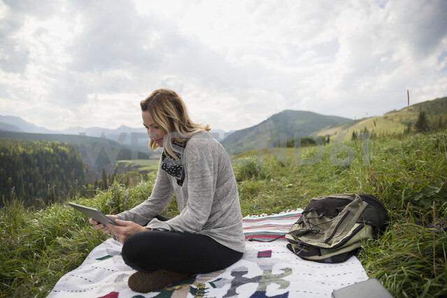 Woman using digital tablet on blanket in remote rural field - HEROF14281