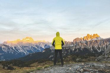 Italy, Tre Cime di Lavaredo, man enjoying colourful mountain peaks at sunset - WPEF01329