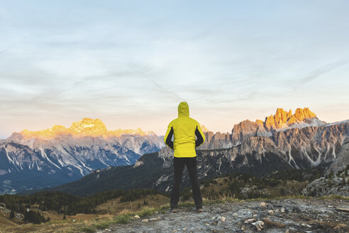 Italy, Tre Cime di Lavaredo, man enjoying colourful mountain peaks at sunset - WPEF01329