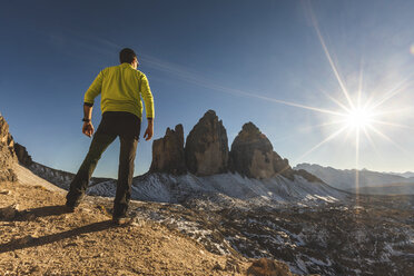 Italy, Tre Cime di Lavaredo, man hiking and standing in front of the majestic three peaks - WPEF01332