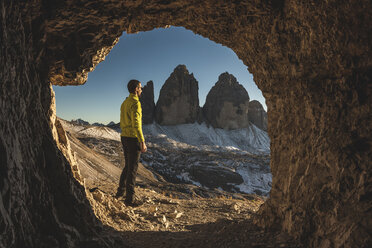 Italy, Tre Cime di Lavaredo, man hiking and standing in front of a cave with the three peaks in background - WPEF01335