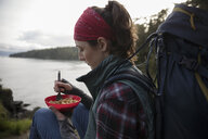 Female backpacker eating cereal on cliff overlooking ocean - HEROF14308