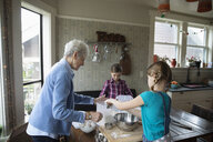 Grandmother and granddaughters baking in kitchen - HEROF14326
