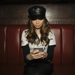 Female millennial using smart phone in nightclub - HEROF14392