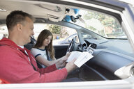 Father with driving manual teaching tween daughter how to drive car - HEROF14404