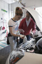 Father teaching tween daughter how to change oil in car - HEROF14407