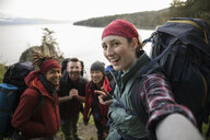 Portrait happy friends backpacking, taking selfie - HEROF14428