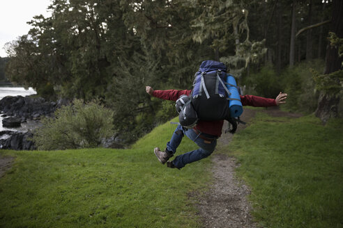 Playful male backpacker jumping for joy on trail in woods - HEROF14431