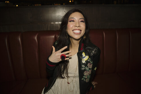 Portrait enthusiastic, confident female millennial with candy ring in nightclub - HEROF14518
