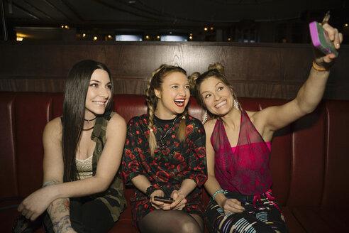 Playful, happy female millennial friends taking selfie in nightclub - HEROF14530