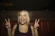 Portrait confident, cool, playful female millennial gesturing peace sign in nightclub - HEROF14548