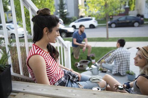 Neighbors gardening, taking a break and talking on front stoop - HEROF14563