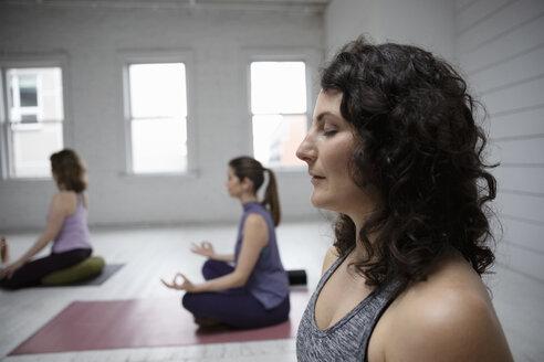 Serene woman meditating in yoga class - HEROF14608