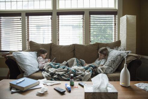 Sick sisters using digital tablets on sofa - HEROF14623