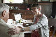 Smiling home caregiver touching senior man - HEROF14626