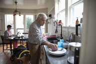 Senior man doing dishes in kitchen with home caregiver working in background - HEROF14629