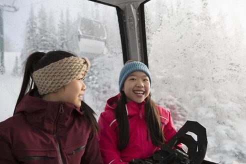 Smiling sister snowshoers riding gondola - HEROF14644
