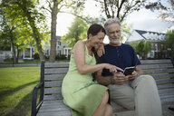 Senior couple using digital tablet on park bench - HEROF14692