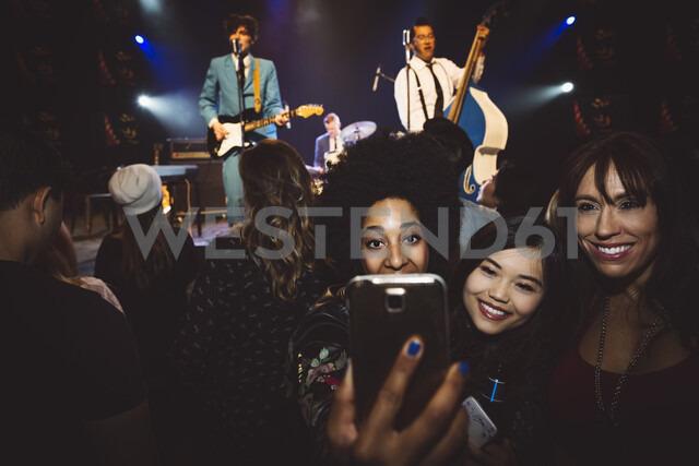 Female milennials taking selfie at music concert in nightclub - HEROF14782 - Hero Images/Westend61