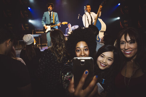 Female milennials taking selfie at music concert in nightclub - HEROF14782