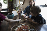 Father and sons grating cheese, making homemade pizza at dining table - HEROF14803