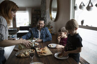 Family eating homemade pizza at dining table - HEROF14806