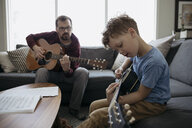 Father teaching son how to play guitar in living room - HEROF14821