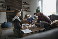 Father and sons assembling model airplane in living room - HEROF14824