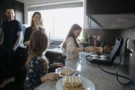 Family making waffles at waffle iron in kitchen - HEROF14833