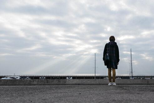 Spain, Barcelona. Vista trasera de un hombre mirando el mar y las nuves en el puerto - JRFF02494
