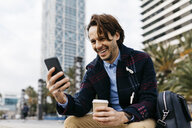 Spain, Barcelona, happy man sitting in the city with takeaway coffee and cell phone - JRFF02503