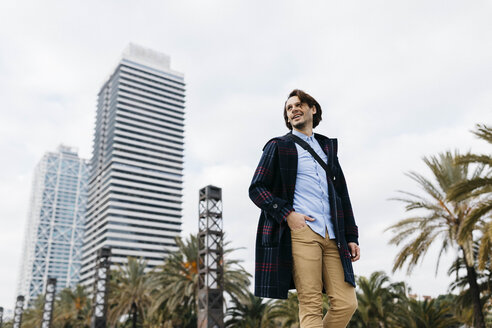 Spain, Barcelona, smiling man walking in the city with two skyscrapers in the background - JRFF02506