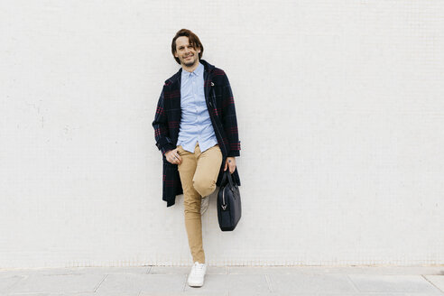Portrait of smiling man with a briefcase standing at a wall - JRFF02509