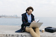 Spain, Barcelona, smiling man sitting at the sea working with laptop and notebook - JRFF02518